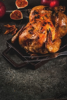 Thanksgiving day food. roasted whole chicken or turkey on dark grey background,  copy space