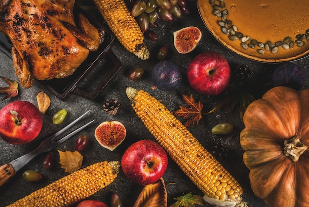 Thanksgiving day food. roasted whole chicken or turkey with autumn vegetables and fruits: corn, pumpkin, pumpkin pie, figs, apples, on dark grey background, top view