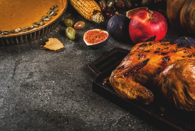 Thanksgiving day food. roasted whole chicken or turkey with autumn vegetables and fruits: corn, pumpkin, pumpkin pie, figs, apples, on dark grey ,