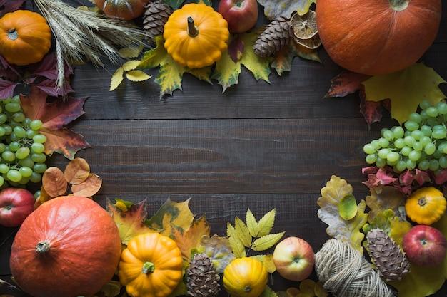 感謝祭。木の板に秋の収穫、カボチャ、カラフルなカエデの葉のフレーム。上面図