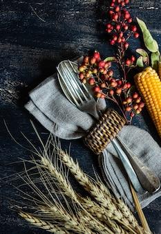 感謝祭の日やナッツ、ベリー、野菜、果物のコピースペースを持つ暗い木製の表面上のフレームと秋の収穫のコンセプト