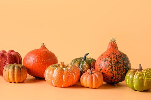 感謝祭やハロウィーンのさまざまなカボチャがオレンジ色の背景に収穫されます。