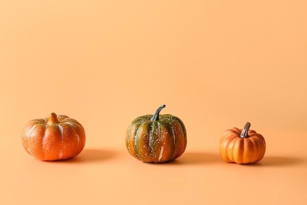 感謝祭の日またはハロウィーンのオレンジ色の背景に異なる3つのカボチャ。