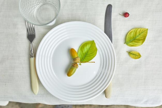 Урегулирование места обеденного стола дня благодарения или хэллоуина декоративное с желудями, листьями на белой предпосылке скатерти, взглядом сверху, взглядом сверху, плоской планировкой.