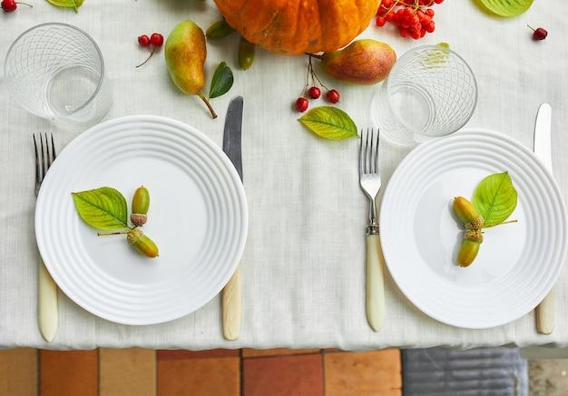 カボチャ、ドングリ、梨で装飾的な感謝祭やハロウィーンの夕食のテーブルの場所の設定は、白いテーブルクロスの背景に葉し、上からの眺め、平面図、フラットレイアウト。
