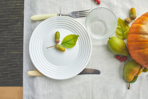 カボチャ、ドングリ、梨の葉で装飾的な感謝祭やハロウィーンの夕食のテーブルの場所の設定白いテーブルクロスの背景