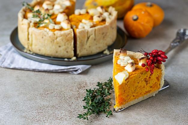 感謝祭のパンプキンフェタチーズとタイムのおいしいパイ秋の伝統的な自家製パンプキンパイ