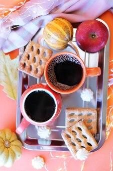感謝祭の日2杯のコーヒーメレンゲカボチャリンゴは家の快適さの家族の休日の概念を残します