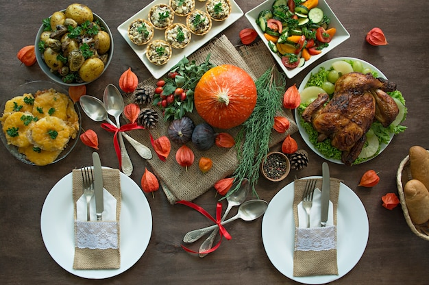 Thanksgiving dinner. halloween dinner. festive table with chicken and all side dishes.