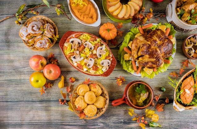 Ужин в честь дня благодарения. жареная индейка с яблочным пирогом, тыквой и булочками с корицей.