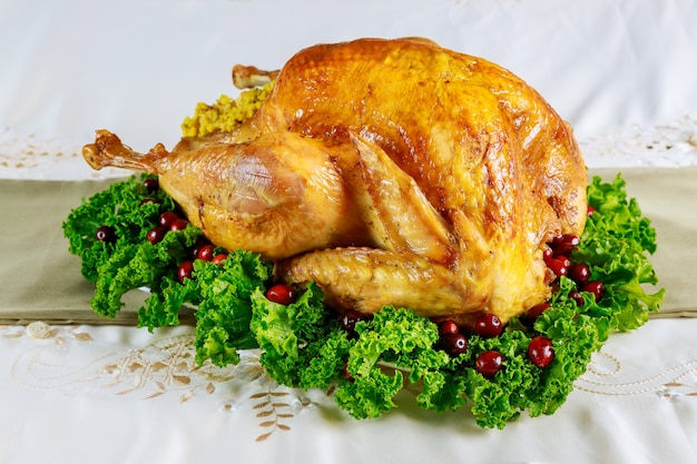 Thanksgiving dinner table served with turkey, decorated with kale and cranberry. holiday new year concept.