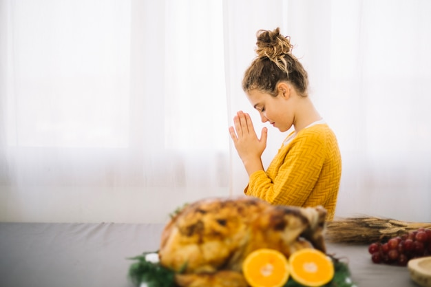 Thanksgiving dishes with side view of woman praying