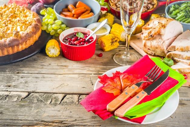 感謝祭の家族の夕食の設定の概念。七面鳥、緑豆、マッシュポテト、詰め物、カボチャ、リンゴとピーカンパイ、素朴な木製のテーブルを使った伝統的な感謝祭の日食