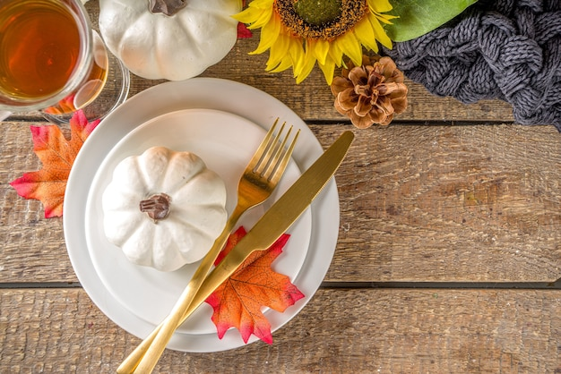 感謝祭の食べ物のコンセプト。プレート、ティーカップ、カボチャ、ひまわりと暖かい格子縞またはセーター、快適で居心地の良いレンガの木の家の表面のコピースペースと秋のテーブルセッティング