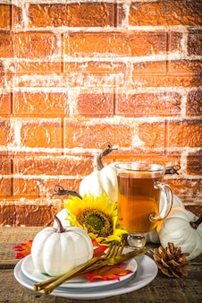 Thanksgiving food concept. autumn table setting with plate, tea cup, pumpkins, sunflower and warm plaid