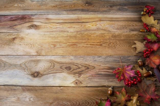 ベリー、どんぐり、秋のカエデの葉と感謝祭の挨拶の背景。季節のシンボルと感謝祭の背景。スペースをコピーします。
