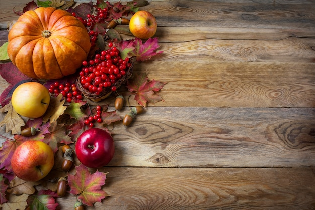 Thanksgiving  greeting background with pumpkins, apples and fall leaves