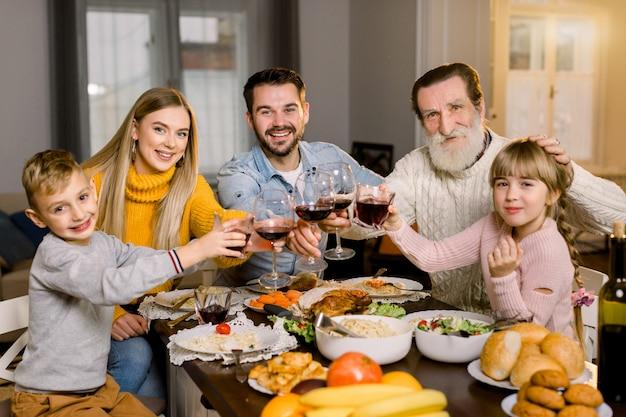感謝祭の休日。幸せな笑顔の家族がテーブルに座って一緒に時間を楽しんで、おいしいディナーを食べて、ワインとジュースのグラスを保持