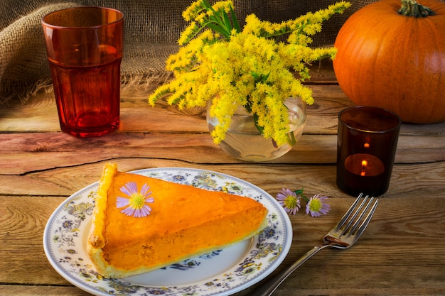 Thanksgiving pumpkin pie slice on the old wooden table