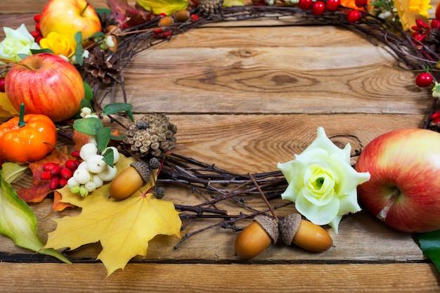 感謝祭のカボチャ、スノーベリー、リンゴ、カエデの葉の花輪、コピースペース