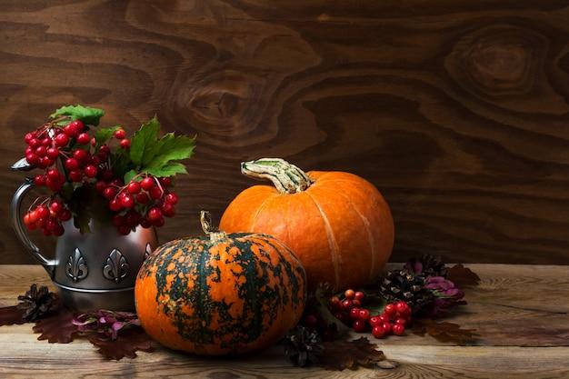 アンティークシルバーのやかんに赤いガマズミ属の木の果実と2つのオレンジ色のカボチャ、コピースペースのある感謝祭の素朴なテーブルのセンターピース