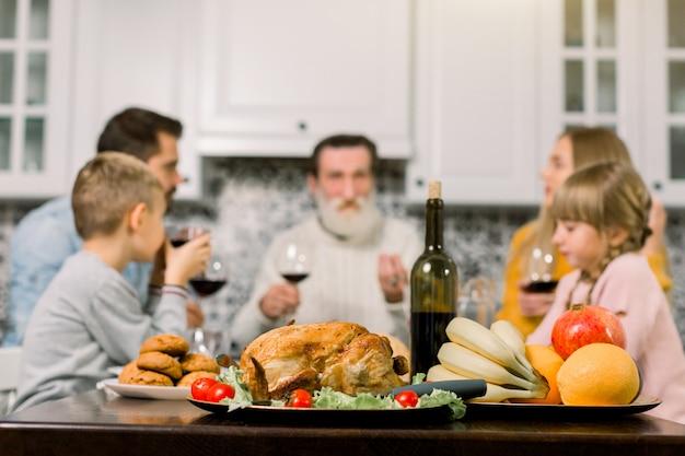 七面鳥、サラダ、クッキー、新鮮な果物、ワインを添えた感謝祭のテーブル。背景のテーブルで幸せな家族