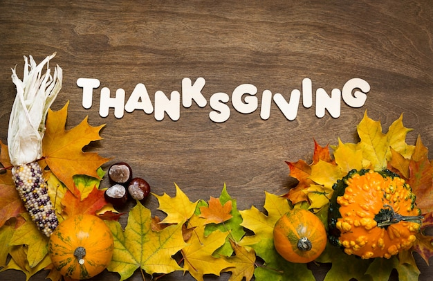 Thanksgiving text with pumpkins, corn and chestnut and maple leaves over wood background.