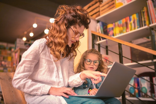 That is great. pleased freelancer sitting near her daughter while staring at screen of laptop