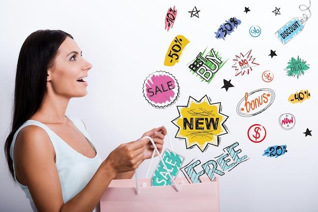 それはすごい!ショッピングバッグを運ぶドレスを着て驚いた若い女性の側面図