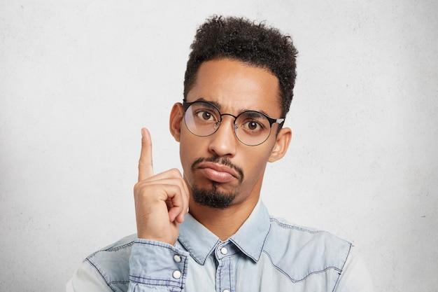 あれは!深刻な黒い肌の男が華麗なまたは壮大なアイデアを得てポーズをとるときに人差し指を上げる