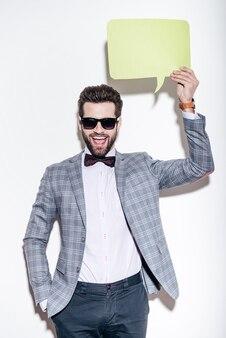 Вот что я говорю. красивый молодой веселый человек в костюме смотрит в камеру с улыбкой и держит зеленый речевой пузырь на голове, стоя на белом фоне