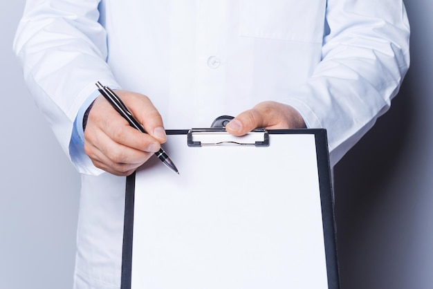 That is what you need! close-up of doctor pointing copy space on his clipboard while standing isolated on white