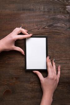 Это идеальное место. женщина руки, держа белую рамку на деревянном фоне. подвешивание диплома или аттестата