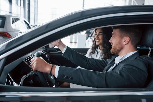 좋아 보인다. 자동차 살롱에서 새 차를 시도하는 사랑스러운 성공적인 부부