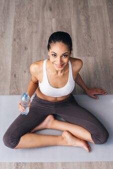 Это была хорошая тренировка! вид сверху красивой молодой африканской женщины в спортивной одежде, смотрящей в камеру с улыбкой и держащей бутылку с водой, сидя в позе лотоса на полу