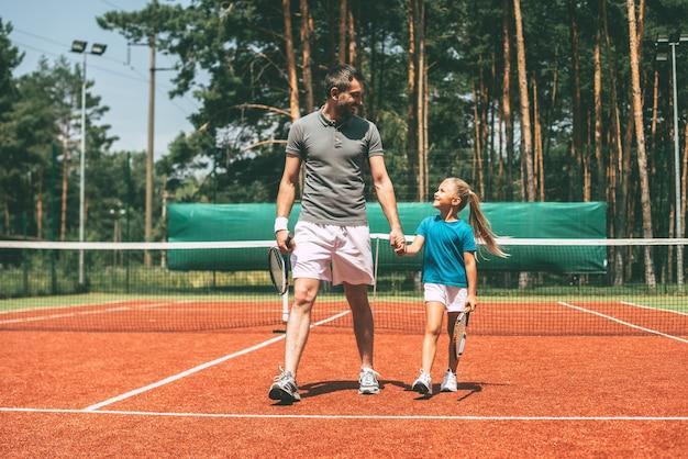 それは素晴らしいゲームでした!テニスラケットを運び、テニスコートで彼女の近くを歩いている彼女の父親を見ているスポーツウェアの小さなブロンドの髪の少女の全長