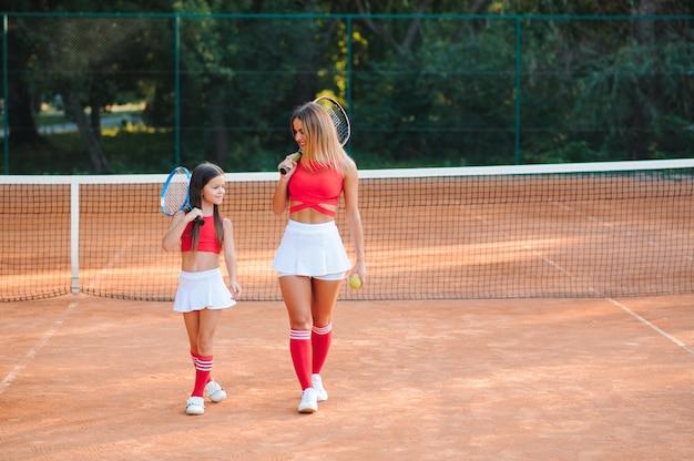 それは素晴らしいゲームでした!小さな女の子のテニス選手と彼女の女性のテニストレーナーの全身ショット