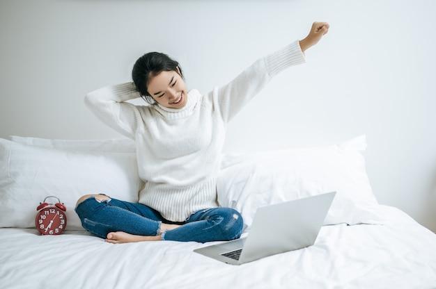 その女性はベッドに座って手を挙げ、ラップトップを枕の上に置きました。