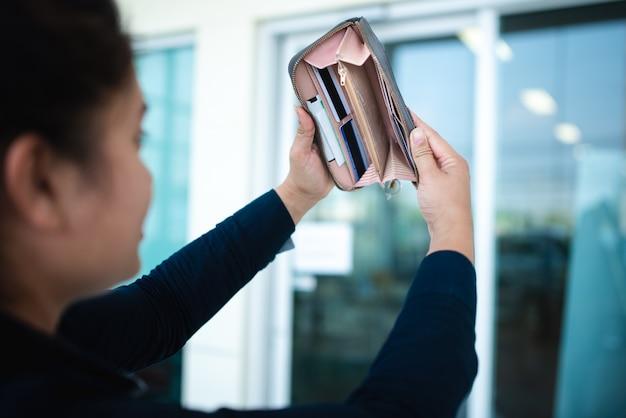 그 여자는 실직 상태 였고 돈이없는 지갑을 주머니에 보았습니다. 그녀는 실직 상태이며 새로운 일자리, 경제 침체 및 희망없는 위기의 개념을 기다리고 있습니다.