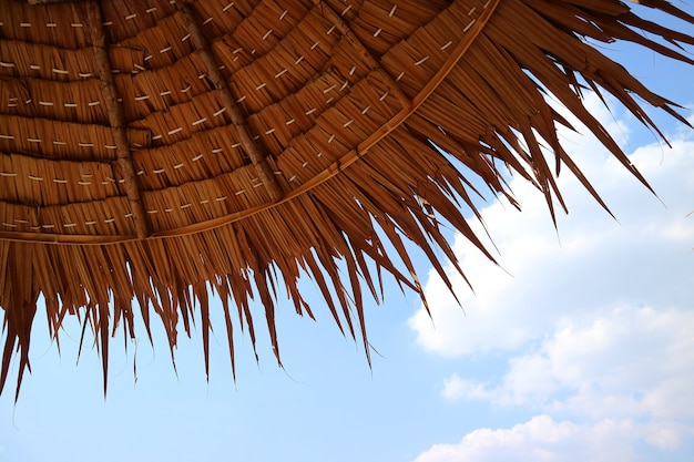 Thatched beach parasol against blue sunny sky