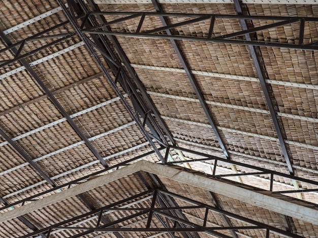 Thatched roof with the metal and wooden frame.