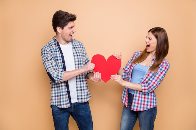 Thats mine! portrait of competitive couple take big red paper card heart pull scream feel crazy have contest lead to divorce wear plaid casual style clothing isolated over pastel color background