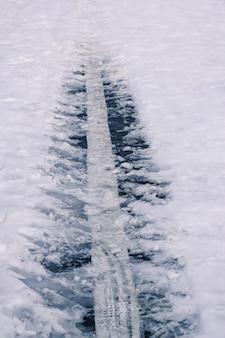 Талая снежная дорога с придорожной разделительной полосой мягкий снег на асфальте в зимний день. скользкая дорога.
