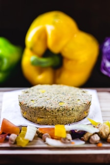 Thawed vegan hamburger, free without meat, made with seeds, vegetables, soy, chickpeas, corn and lychee, surrounded by vegetables