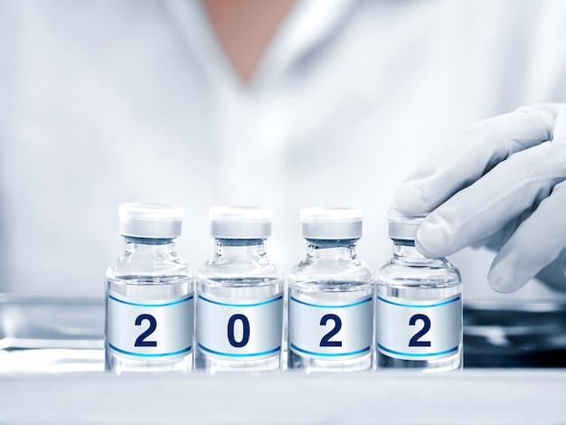 장갑을 끼고 손에 든 백신 바이알의 라벨에 2022년 번호가 있습니다. 코로나바이러스 예방 접종의 전염병에 대한 covid-19 바이러스 치료제에 대한 백신 약물이 있는 4개의 유리 병. 예방 접종 개념입니다.