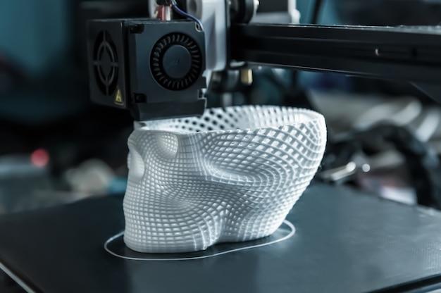 3d-принтер печатает белую пластиковую модель черепа. современные технологии.