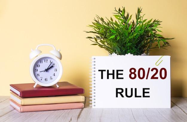 80 20 규칙은 녹색 식물 옆에있는 공책과 다채로운 일기에 세워진 흰색 알람 시계에 기록되어 있습니다.