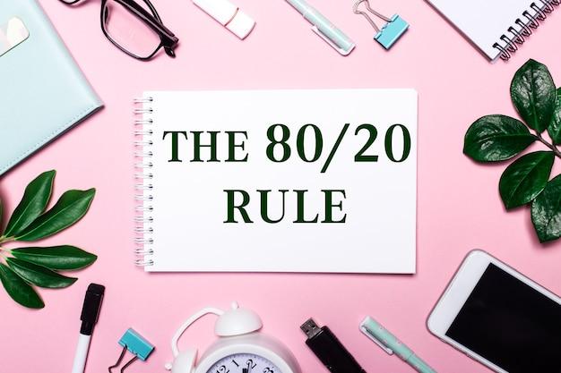80 20 규칙은 비즈니스 액세서리와 녹색 잎으로 둘러싸인 분홍색 배경에 흰색 노트북에 기록되어 있습니다.