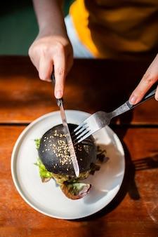 上の手の図は、白いプレートで提供される、ワカモレ、マンゴーサルサ、新鮮なサラダをナイフとフォークでトッピングしたブロッコリーキノアチャコールバーガーをカットします。菜食主義者のための創造的なビーガンミール。