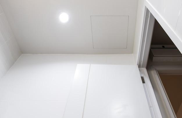 Дверь на белом потолке в ванной для обслуживания электрической системы.